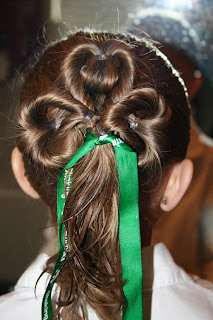 "Back view of young girl modeling ""Three-Leaf Clover Twists"" hairstyle with green ribbon accessory"