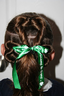 "Back view of young girl's modeling ""Best Three-Leaf Clover"" hairstyle with green ribbon hair accessory"