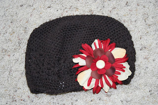 Product photo of chocolate-brown beanie with a red and cream big flower