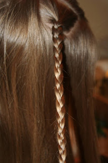 "Side view of young girl's hair being styled into ""Teen Slide-Up Braid"" hairstyle outside"