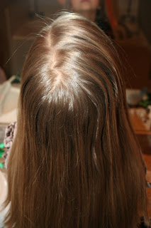 "Back view of young girl's hair being styled into ""Teen Slide-Up Braid"" hairstyle outside"