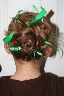 """Back view of young girl modeling """"Messy Bun"""" hairstyle styled with green ribbon hair accessory"""