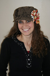 A woman with long hair smiling and wearing a hat