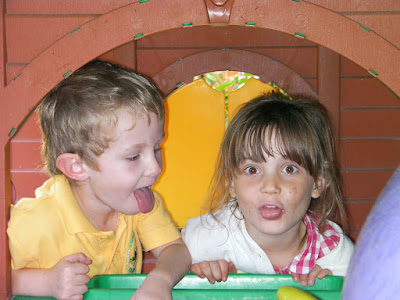 grubby children sticking tongues out b+q garden playhouse