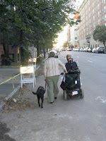 """Image of a dog, woman, and man using a wheelchair walking away. Photo by John B. Kelly, titled: """"No Room on this Sidewalk for You!"""""""