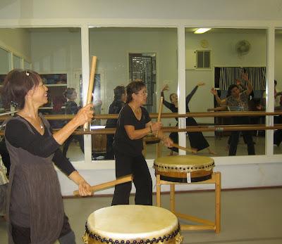 Members of Hawa, Drumming. L. Vera Leo, Center, Annie Ong Class dancing as seen through wall mirrors.