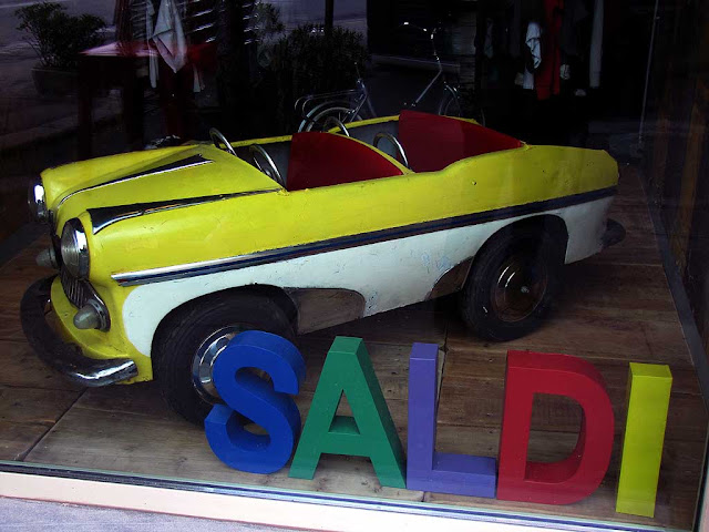 Clothes shop windows, toy car with sales sign, Livorno