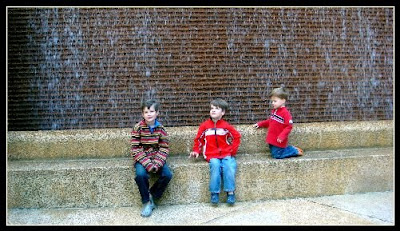 three boys in front of one of the many fountains in Thanksgiving Square