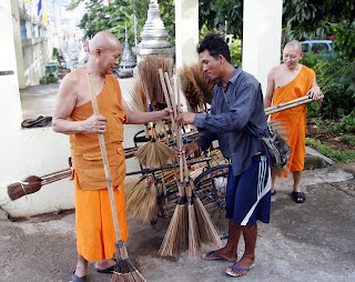 Buying new straw brooms at the temple