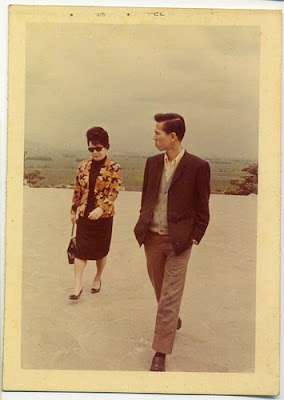 A '60s (maybe) photograph of an Asian woman and her adult son strolling along the pavement.