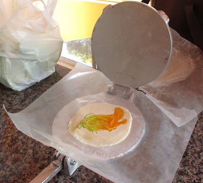 Use a tortillas press to put the zucchini flowers onto the tortilla dough