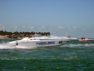 High speed boats racing past the island Sunset Key in the Key West harbor.