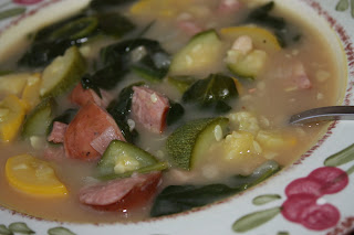 bowl of soup with sausage, beans, squash, and zucchini