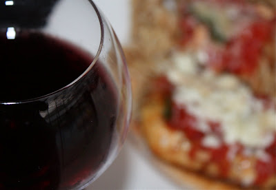 glass of red wine with chicken parmesan dish out of focus in the background