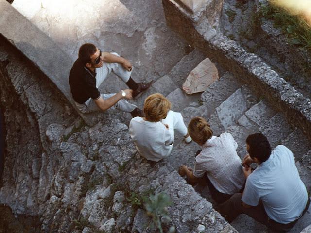 Una mujer y tres hombres sentados en los escalones.
