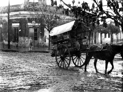 Luvia sobre  las calles de tierra  del pueblo mientras pasa un carro