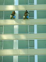 En lo alto de un frente vidriado dos operarios limpiando vidrios.
