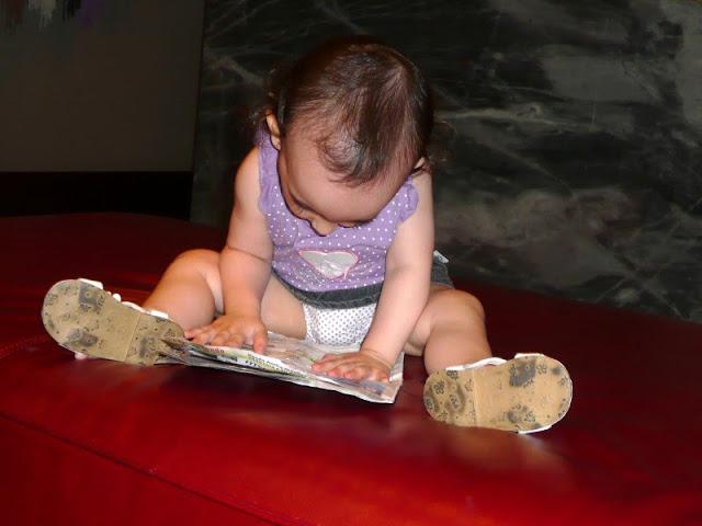 Instantáneas, nena sentada en el piso con una revista.