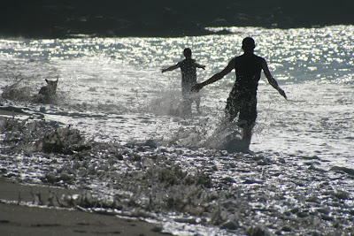Running silhouettes through the surf
