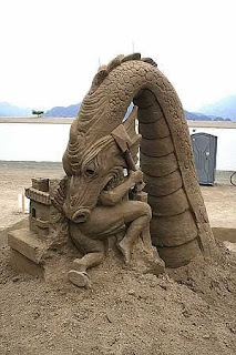 dragon comiendose una persona, escultura de arena