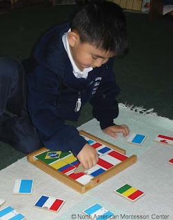 NAMC montessori education nurturing concentration in child respect observation modeling behavior using flag puzzle