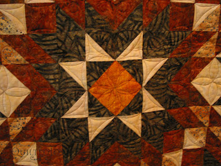 The center star relies on continuous curves and vines that grow out into the star points - QuiltedJoy.com