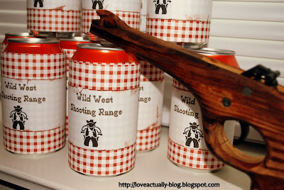 "Soda cans that read ""Wild West Shooting Range"" and a wooden rubber band gun."