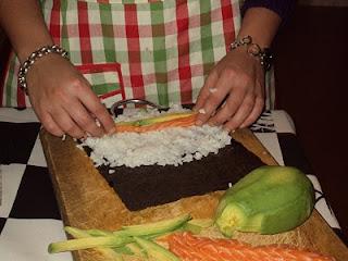Disposizione dell'alga, riso, salmone e avocado per fare i maki