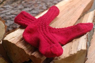 Red wool socks in Broad Spiral Rib, displayed on the woodpile