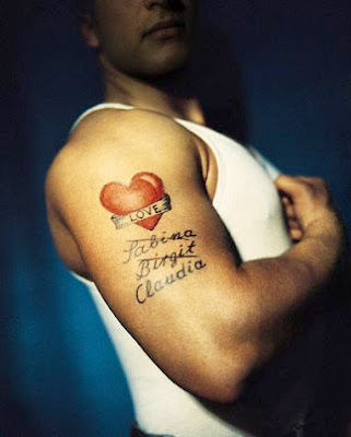 Picture A Men With Heart Tattoo And Letter Tattoo Design On The Arm