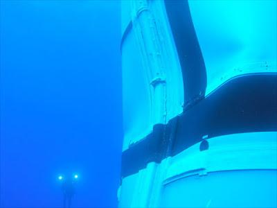 Bajo el agua, el SRB del Ares I-X con un buceador de fondo