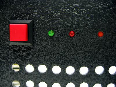 Фрагмент лицевой панели. Здесь расположены: кнопка включения, индикатор включения, индикатор жёсткого диска и утопленная кнопка перезагрузки.