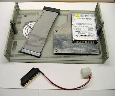 На фото показана доработанная верхняя крышка с креплениями, укороченный IDE-шлейф, жёсткий диск WD800BEVE ёмкостью 80 Гб и переходник для него с разъёмом питания. Последний аксессуар использован по причине устаревшего IDE-шного диска. Если диск будет SATA, то всё можно сделать гораздо проще.