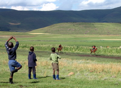 """Some young kids in gum boots rooting on the jockeys near the """"finish line."""