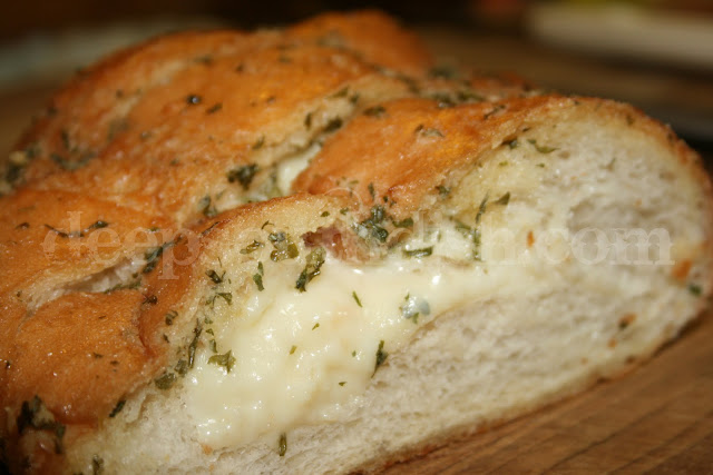 A decadent buttery garlic French bread stuffed with gooey cheese and sprinkled with garlic powder and parsley. An indulgence for sure.
