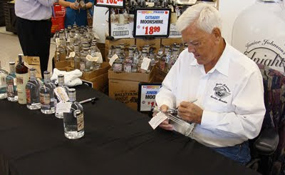 Junior Johnson autographing bottles of Midnight Moon