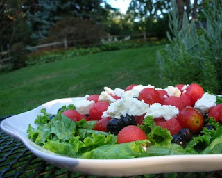 Summer fruit in a gorgeous dressing, atop greens