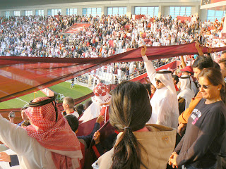 Qataris wave a banner in support of their team