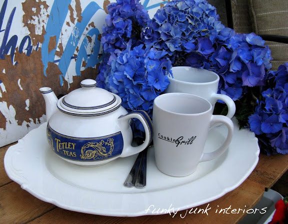 Tea time is served out by the pool in white dishes and blue hydrangeas.