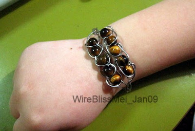 Braided infinity bracelet combining braiding (4 wires) and tiger eyes around the wrist