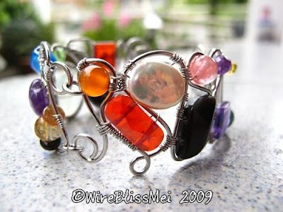 cuff is wire wrapped with various gemstones, pearls and Czech beads