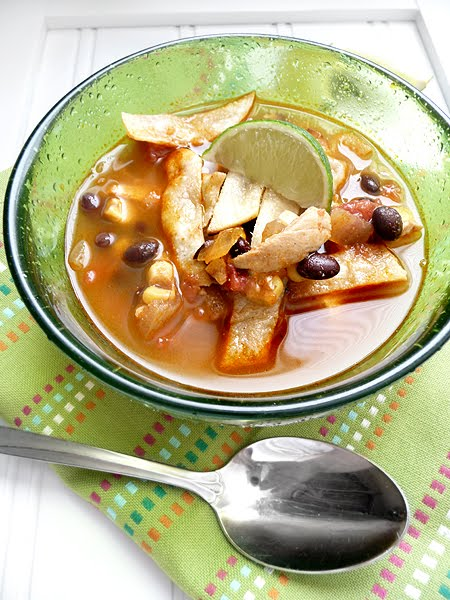 A bowl of homemade chicken tortilla soup, with a spoon resting on the side