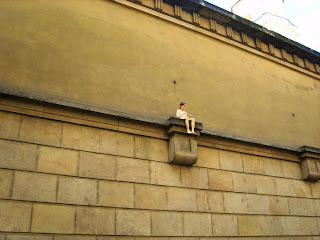 Девочка сидящая на стене университета в Праге