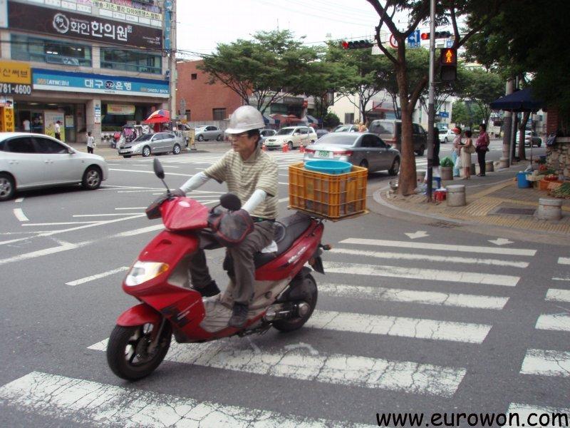 Motorista coreano con cas de obra cruzando u paso de peatones con semáforo en rojo