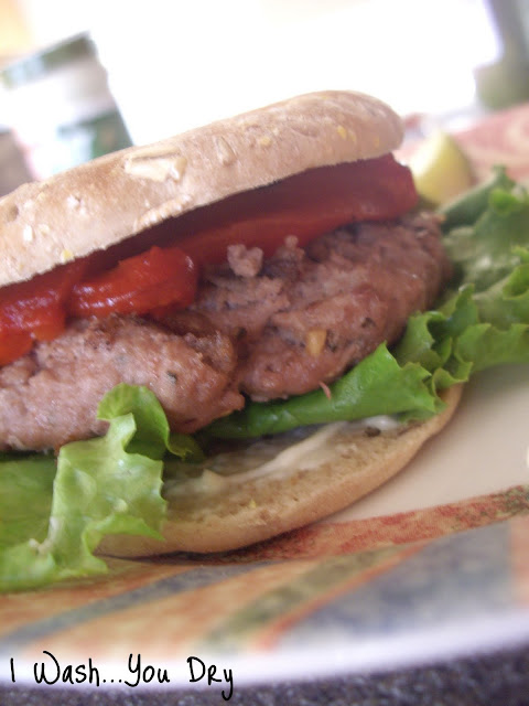 A turkey patty, lettuce, tomatoes between two buns.