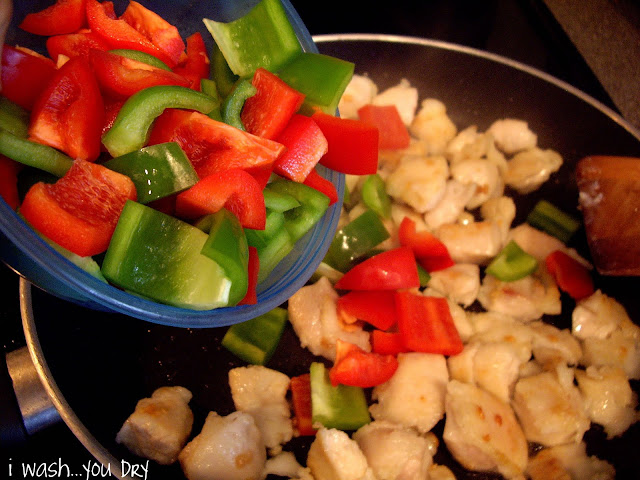 Chopped peppers added to a skillet of chopped chicken.