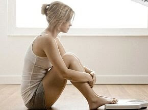 woman sitting infront of bathroom scale