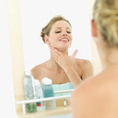 woman applying moisturizer to neck