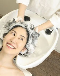 woman getting her hair shampooed at a salon
