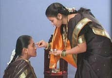 Woman applying kumkum during Haldi Kumkum ceremony